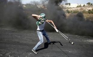 Un Palestinien utilise un lance-pierre pour lancer des projectiles sur les forces de sécurité israéliennes à Beit El, près de Ramallah en Cisjordanie, le 11 octobre 2015