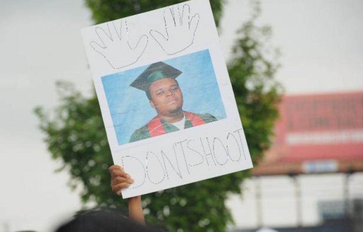 Un manifestant brandit un portrait de Michael Brown, lors d'un rassemblement devant l'église de Greater Grace à Ferguson, Missouri, le 17 août 2014 – Michael B. Thomas AFP