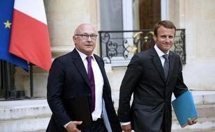 Le ministre des Finances Michel Sapin (à g) et le nouveau ministre de l'Economie Emmanuel Macron quittent le Palais de l'Elysée le 27 août 2014