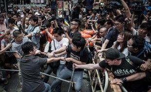 Des manifestants prodémocratie (d) tentent de protéger leur barricade de protestataires adverses (g) dans le quartier de Mong Kok à Hong Kong, le 4 octobre 2014