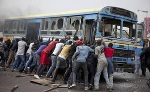 Des manifestants tentent de retourner un bus dans les rues de Dakar (Sénégal), le 1er février 2011.