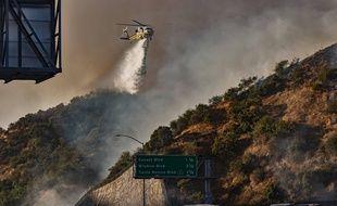Un hélicoptère lutte contre le Getty Fire, un incendie qui s'est propagé le long de l'autoroute 405, à Los Angeles, le 28 octobre 2019.