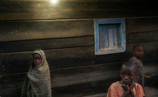 Des enfants devant une maison éclairée par l'électricité à Bugara, le 17 juillet 2016