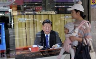 Une femme et son bébé devant une télévision diffusant l'allocution de Xi Jinping, à New Taipei City, le 2 janvier 2018.