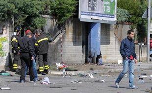 Des policiers italiens inspectent le site de l'explosion d'une bombe devant un lycée à Brindisi, sud de l'Italie, le 19 mai 2012.