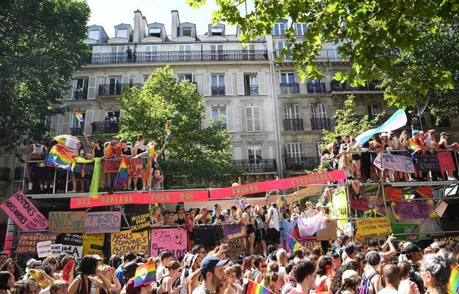 EDITORS NOTE: Graphic content / Participants wave rainbow flags and display placards from a scaffolding as others march by during the annual Gay Pride parade, a 5.5km march from Montparnasse to Republique, in Paris on June 29, 2019. (Photo by Christophe ARCHAMBAULT / AFP)