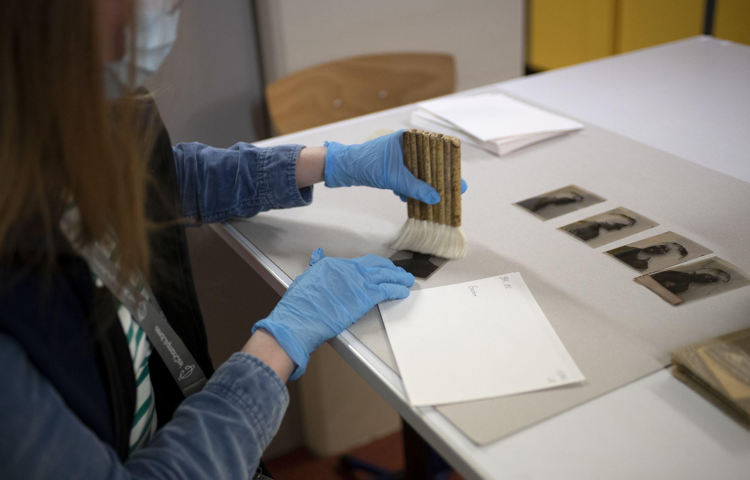 Avant leur numérisation, les vieilles photos sont dépoussiérées et reconditionnées par des historiennes archivistes.