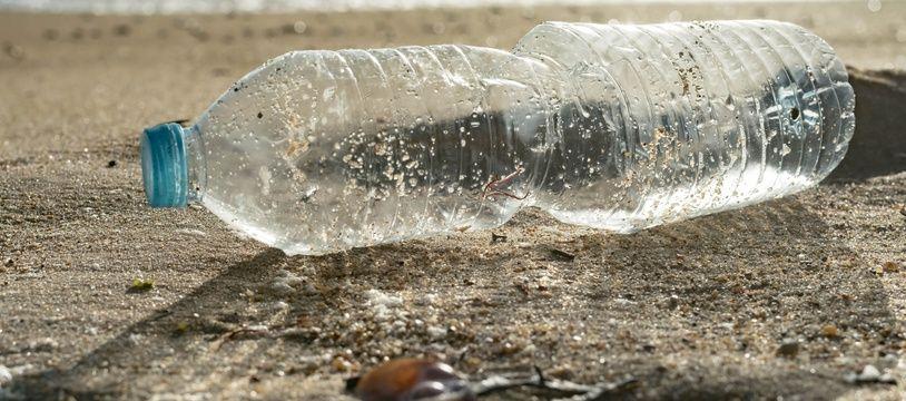 Une bouteille en plastique échouée sur une plage.