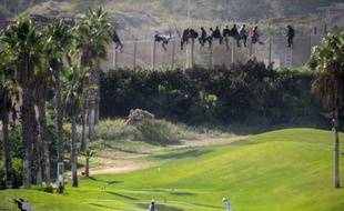 Des migrants sur la barrière de sécurité de l'enclave espagnole de Melilla le 22 octobre 2014