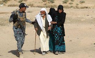 Des familles originaires du village de Bajwaniyah, à 30 km de Mossoul, ont fui la zone de combat, aidées par les membres des forces de sécurités, le 18 octobre 2016