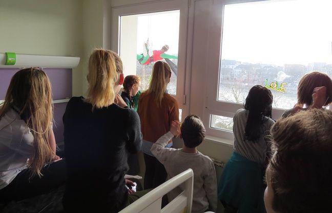 Des enfants malades regardent des super héros par les fenêtres du CHU de Nantes.