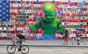 Man cycles past huge colorful mural on Houston Street NYC