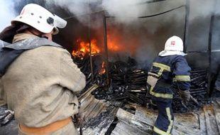 Des pompiers éteignent le 3 juin 2015 un incendie dans un marché de Donetsk, dans l'est de l'Ukraine, provoqué par les combats entre l'armée et les forces séparatistes prorusses
