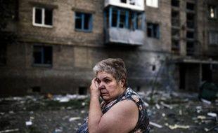 Sous le choc, une femme dans une rue de Yasynuvata près de Donetsk en Ukraine après un pillonage de son quartier, le 12 août 2014