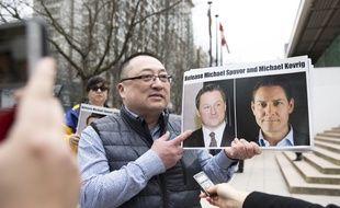 Les photos de Michael Kovrig et Michael Spavor brandies par un manifestant à Vancouver en mars 2019.