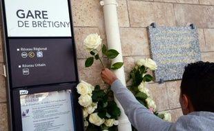 Un homme dépose une fleur à la gare de Brétigny-sur-Orge,  le 12 juillet 2014, un an après la catastrophe qui a causé la mort de 7 personnes