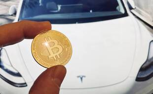Une représentation d'un Bitcoin devant une voiture Tesla.
