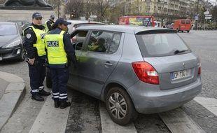 Paris, le 17 mars 2014. Des policiers contrôlent les véhicules alors que la circulation alternée est mise en place.