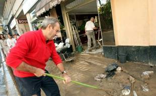 Des habitants nettoient les boutiques et trottoirs à Cannes après les inondations, le 4 octobre 20105 dans le sud-est de la France