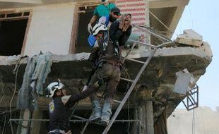 Des bénévoles du service de défense civil syrien évacuent des gens d'un immeuble détruit par des bombardements, dans un quartier rebelle d'Alep le 23 avril 2016