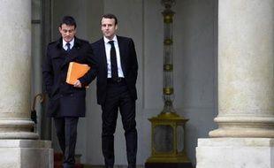 Le Premier ministre Manuel Valls (g) et le ministre de l'Economie Emmanuel Macron quittent l'Elysée le 10 décembre 2014