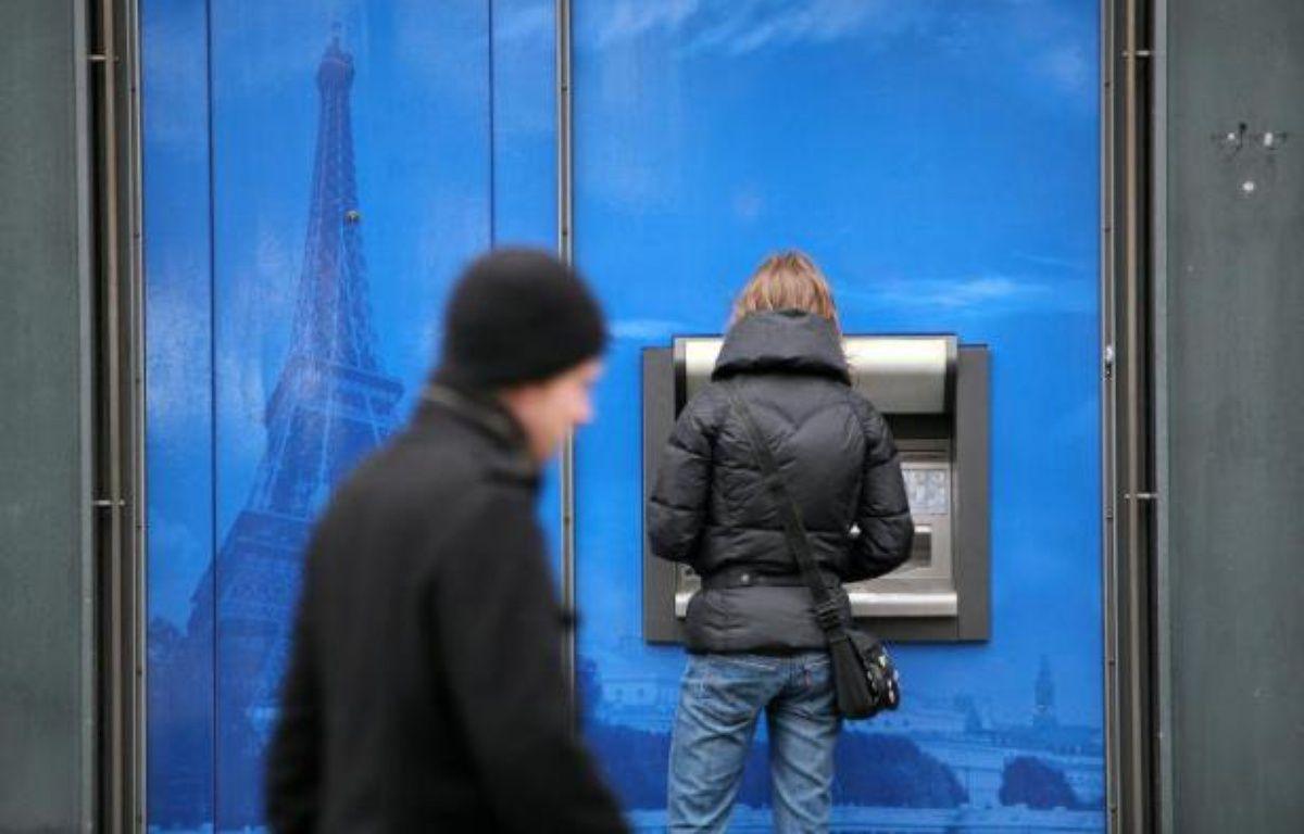 Une femme retire de l'argent dans un distributeur à Paris – Loic Venance AFP
