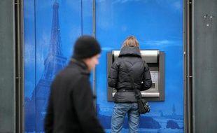 Une femme retire de l'argent dans un distributeur à Paris