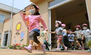 Des enfants japonais portent des masques à la crèche, le 10 juin 2011, à Iwaki dans la préfecture de Fukushima.