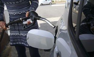 Illustration d'une personne se servant d'une pompe à essence dans une station service.