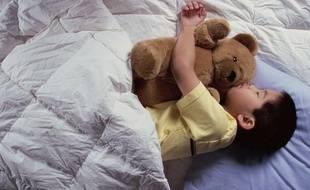 Un garçon en train de dormir avec son ours en peluche.