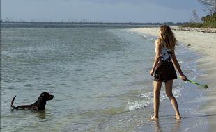 Une jeune femme joue avec son chien sur la plage en Floride.