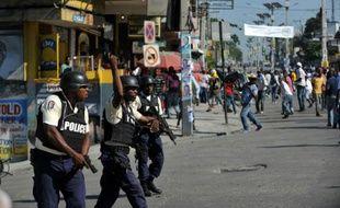 Un policier tire en l'air lors de heurts avec des manifestants, le 24 novembre 2015 à Port-au-Prince, en Haïti