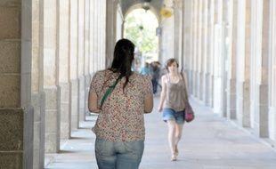 Des femmes marchent sous les arcades de République, à Rennes.