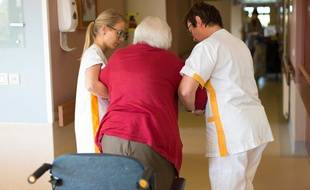 Illustration. Deux infirmiers aident une personne âgée dans une maison de retraite.