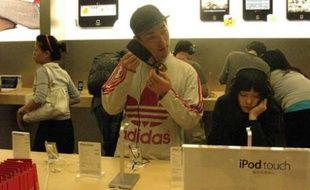 Des clients pékinois testent les produits Apple jeudi dans le premier iStore de Chine, inauguré à Pékin le 19 juillet. C.DIJKHUIS/20 MINUTES