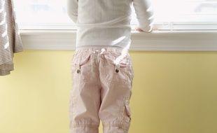 Illustration d'un enfant devant une fenêtre.