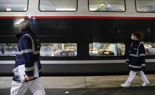 Du personnel soignant marche devant un train reliant Paris à la Bretagne et transportant des malades du Covid-19, le 31 mars 2020.