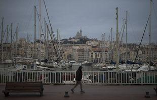 Un homme marche le long du Vieux-Port de Marseille avant l'application du couvre-feu, le 10 janvier 2021.