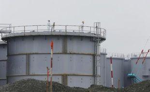 Des employés travaillent sur une citerne contenant de l'eau contaminée à la centrale nucléaire de Fukushima Daiichi au Japon, le 12 novembre 2014