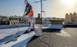 Pose de la peinture blanche mise au point par Cool Roof sur un toit de Paris.