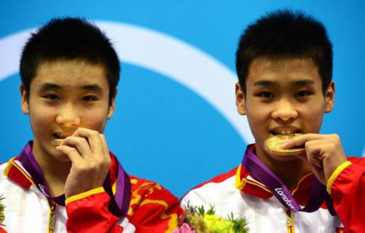 China's gold medalists Cao Yuan and Zhang Yanquan pose on the podium after the men's synchronised 10m platform final diving event at the London 2012 Olympic Games at the Olympic Park in London on July 30, 2012. AFP PHOTO / CHRISTOPHE SIMON – Christophe Simon afp.com