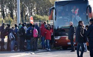 Des associations accompagnent de jeune migrants vers un bus qui va quitter Calais vendredi 28 octobre.