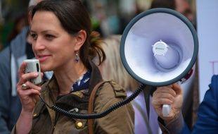 Une femme manifeste, avec un mégaphone. Photo d'illustration.