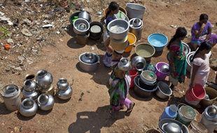 Des femmes rassemblent des sceaux pour collecter l'eau à une fontaine public dans la banlieue d'Hyderabad, en Inde.