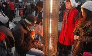 Des usagers des transports en commun se réchauffent à la gare du nord, le 12 mars 2013.