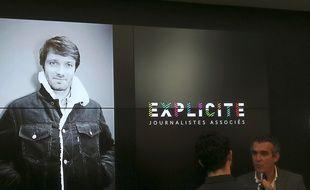 Olivier Ravanello en interview devant le logo d'Explicite et la photo d'Antoine Genton, journaliste associé, lundi, durant la conférence de présentation d'Explicite.