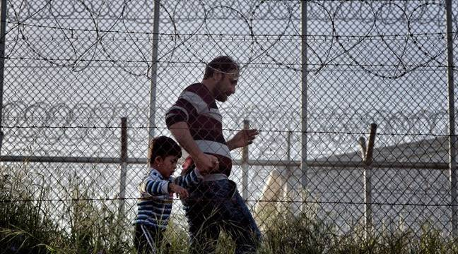 Un homme et son enfant dans le centre de détention à Mytilène en Grèce, le 15 avril 2016. – ARIS MESSINIS / AFP