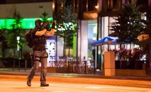 Un policier à Munich près du centre commercial où a eu lieu la tuerie qui a fait au moins 10 morts le 22 juillet 2016.
