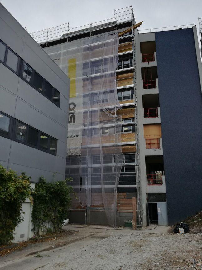 Les panneaux en fibre de bois sont actuellement fixés, avec de la colle et des chevilles, sur la façade du bâtiment.