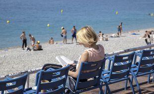 Une femme lit sur la Promenade des Anglais à Nice